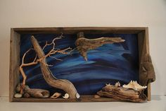 """An organic, dimensional wall art depiction of ocean & beach life, utilizing various corals, seashells, and driftwoods shaped by time, wind, and sand entombed in a vintage wooden crate, adorned with shades of azure as a backdrop. Made entirely in the U.S.A. Dimensions: 18"""" Ht. x 34"""""""