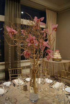 The tall centerpieces featured gold manzanita branches with pink cymbidium ...  triasflowersblog.com
