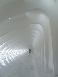 Milwaukee Art Museum ~ photo by Katie Tegtmeyer.  A long, white hallway, with repetitive arches.  It creates interesting light & shadows along the way.