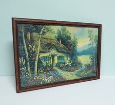 This enchanting print features a most charming thatched roof cottage beside a serene pond. Nestled in an English garden of riotous color, it is in the