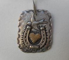 """soft edged square sterling silver disc with a 14 K yellow gold heart.  Embraced by a detailed horse shoe, topped by a flying swallow and stamped all around the edges. Great hand hammered bail. Measures 1.25"""" by 1.5"""""""