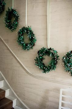 Faux mistletoe and green apple twig wreaths hung by ribbon up the staircase. Homes & Gardens January 2011. Photographer Paul Raeside.