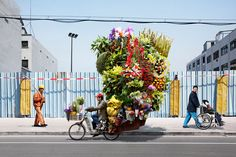 anthropologie: Alain DeLorme's Totems series showcases precarious stacks of things—flowers, tires, office chairs—being transported to and fro within his photoshopped version of Shanghai. Image via: Alain DeLorme interesting thought: stacks, stacking & We Are The World, People Of The World, Totems, Le Totem, Illustration, French Photographers, French Artists, Flower Delivery, Belle Photo