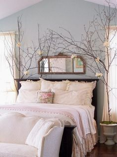 adult romantic room decoration pale blue walls white bed linen shrubs white flowers