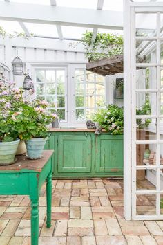 The sideboard serves as a potting table, built of old doors and floorboards. Get more inspiring ideas... Greenhouse Shed, Greenhouse Gardening, Greenhouse Wedding, Simple Greenhouse, Window Greenhouse, Portable Greenhouse, Balcony Gardening, Garden Planters, Garden Wedding