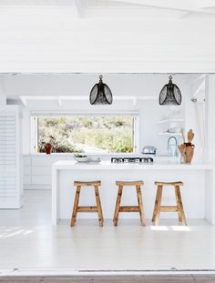 All-white beachy kitchen: white floorboards, white handleless cabinets/drawers, white island bench with stone waterfall edge, wooden bar stools, white weatherboard walls, black pendant lights