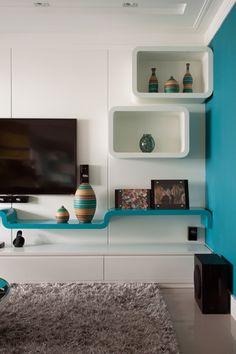 A parede revestida em papel de tecido azul faz a discreta divisão entre a sala de TV e a de jantar.