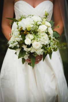A simple and elegant bridal gown with a white and green bridal bouquet. | A Simple Wedding Dress for a Lakeside Ceremony