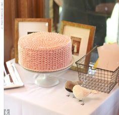 The simple cake was covered in pink vanilla buttercream ruffles. Family wedding photos and two birds finished off the cake table.