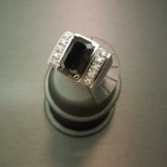 Man's Art Deco White Gold 6.30ct Black & White Diamond Ring Constructed of 14KT White Gold Containing 1 Emerald cut Natural Black Diamond in center weighing 5.80cts & 10 surrounding Round White Diamonds totaling .50cts Finger Size 9 3/4 Ring weighing 14 grams  Item Number:  WS1821