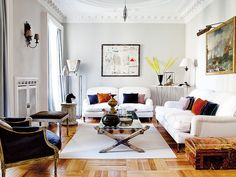 An eclectic Madrid living room filled with antiques, silk velvet cushions & contemporary art
