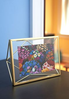Memorable Dimension Frame | Just as memories float in your mind, so do your most-treasured photographs suspend when displayed in this prism-shaped picture frame. Bordered by a 3-dimensional brass wire frame, your 4x6 photo sits between two glass panes and can be exhibited on the wall with the included hardware, or set upon a desk or side table.