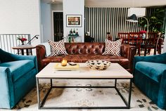 Living room with leather couch and teal, velvet armchairs