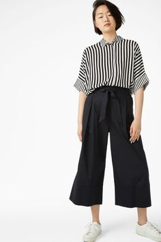 A polished pair of paperbag waist culotte pants, with a half-elasticated sash waist, hidden pockets, and wide cuff details at the hems. Search 0499973 on site.