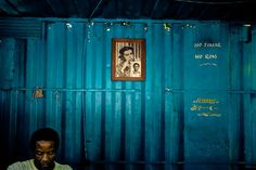 A Cuban man works in front of a portrait of the Revolutionary leader Che Guevara, hung on the wall of a movable locksmithery in Alamar (the Eastern Havana), Cuba.