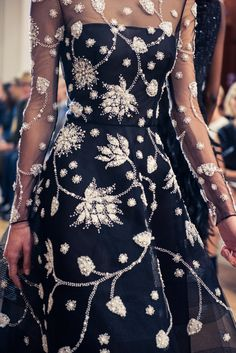 Oscar de la Renta's Spring 2017 Collection: black, empire waist, sheer long-sleeve dress with white floral embroidery and beading  | coveteur.com