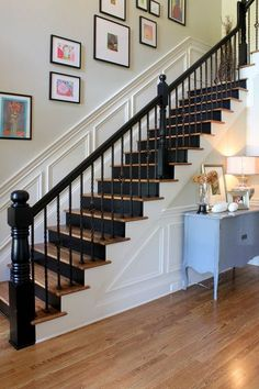 How to update old stairs- stain the steps to match wood floors, then paint the risers and railings black. Add picture frame moldings to the wall and voila!