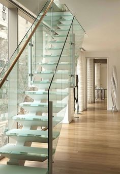 White staircase with glass balustrade, facing window wall