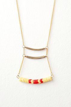 african snake bead ladder necklace with brass curved bars on a gold plated curb chain