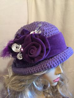 This is a crocheted hat that I decorated in the style of Downton Abbey. It has 2 Cabbage Roses that I created out of repurposed velvet fabric. The band is made out of the same purple velvet fabric and Feathers surround the flowers. I also created a Faux Hat Pin.  It is an acrylic yarn and is nice and warm as well as stylish.  It is an average size hat!!!  What fun to wear...it makes you feel so special