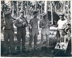1943- Catholic chaplain hands out baseball gear to U.S. Marines on a South Pacific island.