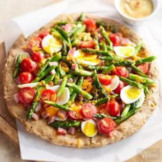 Spring Breakfast Pizza with Spiced Hollandaise: Fresh asparagus, sliced hard-cooked eggs, cheese, cherry tomatoes and diced ham top an easy homemade crust. Recipe: http://www.midwestliving.com/recipe/spring-breakfast-pizza-with-spiced-hollandaise/