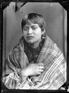 Unidentified Maori woman, wrapped in a plaid blanket/shawl, photographed by William James Harding of Wanganui between 1856 to 1889. She wears a shark? tooth ear adornment, and rings on one of her fingers. She has facial moko.