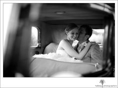 groom kissing bride inside their old fashion getaway car at their Firestone Vineyard Wedding - photo by Halberg Photographers