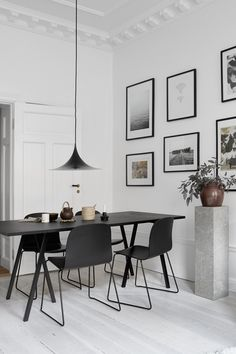 Monochrome dining space with white walls and black Muuto chairs