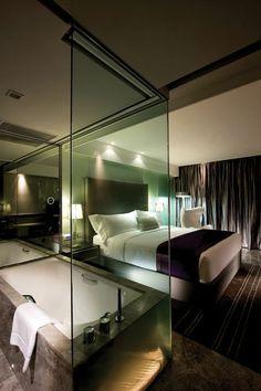 chambre d'hôtel avec jacuzzi, chambre à coucher, paroi de baignoire en verre