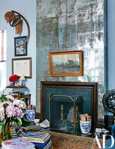 Antiqued mirror panels and 19th-century accessories dress up artist Jack Pierson's Manhattan apartment's existing fireplace | archdigest.com