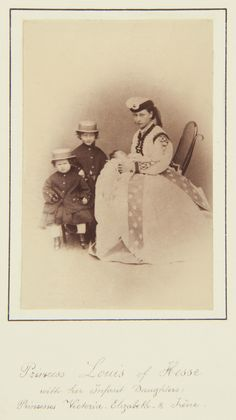 Princess Louis of Hesse with her daughters, Princess Victoria, Princess Elizabeth, and Princess Irene, 1866 - Pss Alice is seated, slightly to left, holding the infant Pss Irene on her lap. Pss Alice looks towards the camera; she wears hat. Psses Victoria (standing) & Elizabeth (seated)