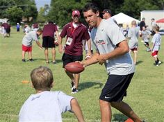 Former Oklahoma quarterback and current St. Louis Rams quarterback Sam Bradford, right, demonstrates how to hand off a football with a camper at his camp at the University of Oklahoma in Norman, Okla., Wednesday, July 11, 2012. (AP Photo/Sue Ogrocki)