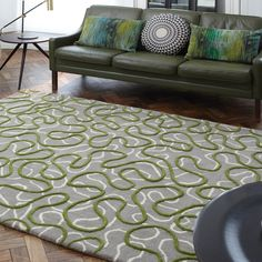 Squiggle Rugs feature a raised green ribbon of colour which has been hand carved to create additional dimension against the grey and cream background.