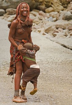A young Himba mother (Namibia) takes some time to playfully enjoy her son.