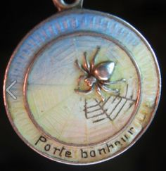 """""""When spiders spin their webs 'fore noon,   sunny weather's coming soon."""" Old enameled spider and web French good luck charm"""