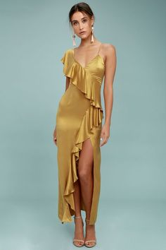The New Friends Colony Evita Gold Maxi Dress is your ticket to a sleek, sophisticated look! Soft silk fabric, in a rich gold hue, drapes across an asymmetrical bodice with a ruffled sleeve and skinny strap. Ruffles continue into a maxi skirt with sexy side slit. Hidden back zipper/clasp.
