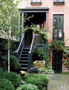 J. Moore - The painted trim of the 1905 house is complemented by matte-black accents found throughout the garden; the window box is planted with English ivy, and a purple sweet potato vine adds a splash of color at the foot of the stairs.
