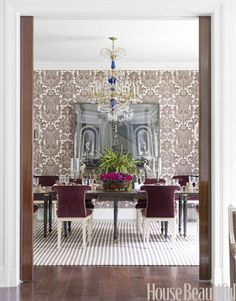 In this dining room, Roberts choose similar colors to tie the rug and wallpaper together.