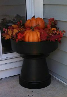 Fall porch decorations. Terra cotta pots glued together and spray painted. Decorative pumpkins and fake leaves.