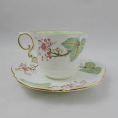 Gorgeous tea cup and saucer set made by Aynsley. Cup is green in center with flowers and leaves decorating the outside. Gold trimming on cup and saucer edges, as well as on handle. Great condition with no chips or cracks (see photos). Please note there is a small amount of fine crazing on