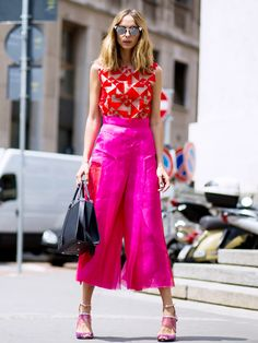 Sheer red patterned top paired with pink culottes and a black structured bag