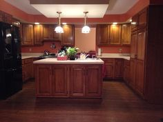 Burnt orange paint is Tomato Bisque by Valspar.  Love the hickory cabinets, oak floors and kitchen island.