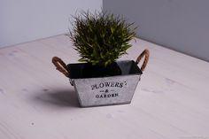 """Metalowa doniczka, która jest ocynkowana. Zdobi ją czarny napis """"flowers garden"""" oraz lutowa linka, znajdująca się po bokach. Idealna pod uprawę pachnących ziół... i nie tylko. Sprawdzi się w domu, na tarasie i ogrodzie."""