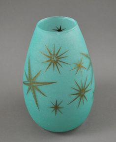 Cool 1950s retro vase. Textured turquoise glass vase with gold starbursts. The gold stars vary in size and design. Very fifties looking! The bottom of the vase is clear. Stands 6 5/8 inches t...