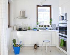 Biała kuchnia nawiązuje wystrojem do reszty mieszkania, nowoczesnego i minimalistycznego, ale mimo to nie jest chłodna i surowa. Ta aranżacja kuchni to proste formy, gładkie powierzchnie oraz funkcjonalizm. Mimo to biała kuchnia sprawia wrażenie ciepłego wnętrza - to zasługa światła, a także wysmakowanych barwnych dodatków.