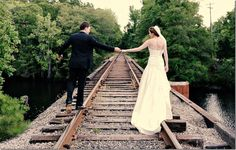 Bride and groom walking down train tracks together - Conway River Walk