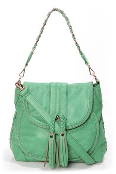 The perfect blend of Bohemian, western, and urban, the Saddle Up Sea Green Handbag by Urban Expressions wears many hats! Matte, sea green vegan leather is finely crafted into a roomy saddlebag with braided trim, exterior zipper pocket, and fringe-y tassels dangling from the front flap. Hidden magnetic closure unsnaps to reveal a front pouch pocket and a zip-top interior with three pockets, plus a cool, floral print lining.