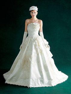ウエストのゴージャスな装飾が華やぎを添えて ウエストにはきらびやかなシルバーレース、スカートの裾には銀糸刺しゅうが贅沢にあしらわれ、ヒロインにふさわしい華やぎを添えています。ドレス¥420,000[レンタル料¥336,000]、手袋(2点共Ar.YUKIKO) 、カチューシャ(キサス ヘアアクセサリーズ)、イヤリング(吉田アクセサリー)、ブーケ(フロレアルオペーク丸の内店)