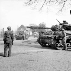 Churchill tanks of 6th Guards Tank Brigade carrying paratroopers from the American 17th Airborne Division pass through Dorsten in Germany, while an Achilles tank destroyer waits, 29 March 1945.